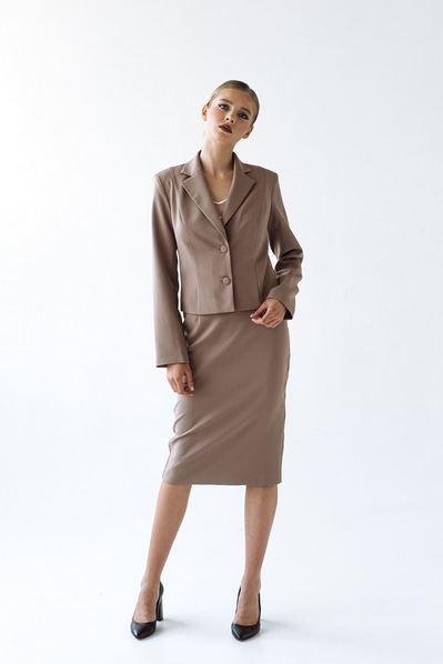 Костюм юбка до колен и приталленый жакет на фоне капучино
